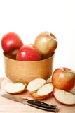 Cut Apples by Whole Apples in a Wood Bowl. Apples in a wood bowl and on cutting board with some cut in half Royalty Free Stock Photo