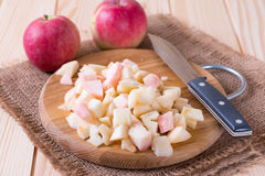 Cut apples on wooden cutting board with a knife Stock Images