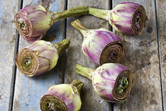 Cut Artichokes on Rustic Table Royalty Free Stock Image