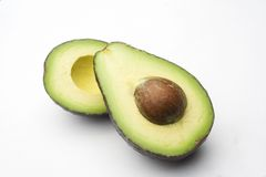 Cut avocado. A cut avocado  with put showing on a white background with shadow Royalty Free Stock Photos