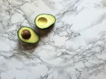 Cut avocado halves with pit on marble countertop with copy space. A fresh avocado has been cut in half and is resting cut side up on a marble surface Stock Photo