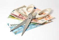 Cut the banknotes. Scissors and several banknotes: cutting the expenses Stock Images