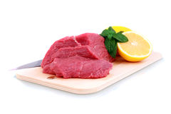 Cut of beef steak. Cut of beef steak, knife with lemon slice. Isolated royalty free stock image
