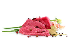 Cut of beef steak with garlic slice, onion and. Laurel. Isolated royalty free stock images