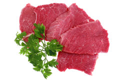 Cut of beef steak with green leaf. Isolated royalty free stock photo