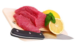 Cut of beef steak, knife with lemon slice. Isolated royalty free stock images