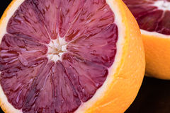 Cut blood orange on black stock images