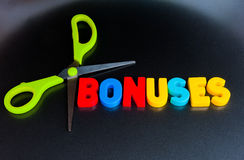 Cut bonuses. Text ' bonuses ' in colorful upper case letters surrounded by the blades of a pair of scissors on a dark background. A concept about bankers' Royalty Free Stock Photo