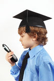 Cut boy in academic hat with a magnifying glass on white background Stock Photography