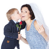 Cut boy groom kissing his cheerful mother bride Royalty Free Stock Image