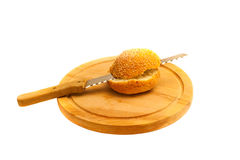Cut bread on a board on a white background. Cut in half on cutting board bun with sesame seeds on a white background Royalty Free Stock Photo
