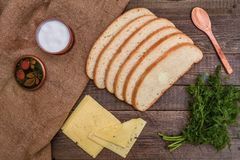 Cut bread, cheese and fennel on a wooden table Stock Photos