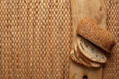 Cut bread showing air texture of flour on wood block with weave background and copy space. stock images