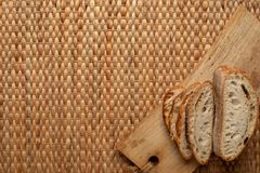 Cut bread showing air texture of flour on wood block with weave background and copy space. royalty free stock image