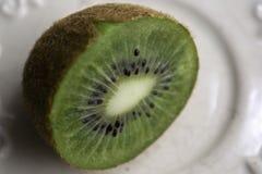 Kiwi half cut lies on a platter royalty free stock image