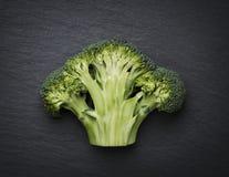 Cut through broccoli  on a stone slab. Stock Photos