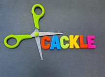 Cut the cackle. Text 'cackle' in colorful uppercase letters with scissors alongside, dark background. Concept of stopping sounds such as squawk, chuckle, jabber Royalty Free Stock Image