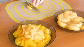 Cut candied peach into slices and put in a plate. Cut into halves of peach and put in a plate stock footage