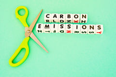 Cut carbon emmissions. Text ' carbon emissions ' inscribed in black uppercase letters on green background with symbolic pair of green handled scissors stock photography