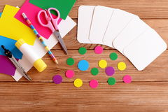 Cut cards and circle, scissors, pencil, glue, colored cardboard sheets on a wooden table. Step Stock Photos