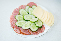 Cut cheese, sausage and cucumber in a plate Stock Images