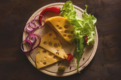 Cut cheese with vegetables. And greens on a round cutting board on a wooden background Royalty Free Stock Photos