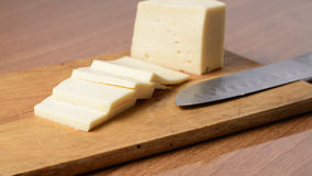 Cut cheese on a wooden board Stock Photos