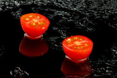 Cut Cherry Tomato on Black with Water Stock Image