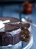 Cut a chocolate cake with butter cream and cherries, holiday Royalty Free Stock Photos