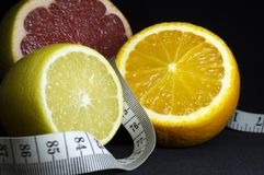 Cut citrus fruits: lemon, orange and grapefruit with measuring tape. Black background. stock image
