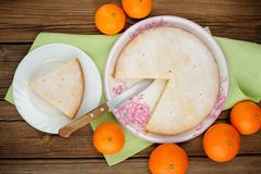 Cut clementine pie with clementines and knife on wooden backgrou Stock Photo