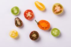 Cut colour tomatoes on white stock images