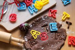 Cut cookies from raw chocolate dough on a wooden table with colorful letters. Cooking traditional Easter biscuits. Easter food stock photography