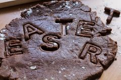 Cut cookies from raw chocolate dough on a wooden table with letters. Cooking traditional Easter biscuits. Easter food concept royalty free stock photo