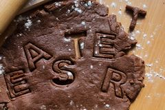 Cut cookies from raw chocolate dough on a wooden table with letters. Cooking traditional Easter biscuits. Easter food concept stock photos