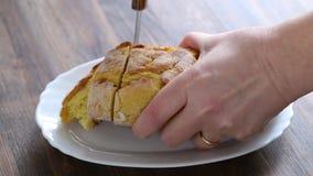 Cut cornbread on white dish on wooden background stock video