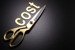 Cut cost. Golden scissors with the text cost Royalty Free Stock Photography
