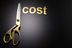 Cut cost. Golden scissors with the text cost and price Royalty Free Stock Photos