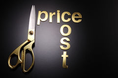 Cut cost. Golden scissors with the text cost and price Royalty Free Stock Photo
