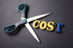 Cut cost. Scissors with text  cost on the black background Stock Photo