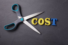 Cut cost. Scissors with text  cost on the black background Stock Images