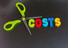 Cut costs. Pair of scissors with green handles enclosing text ' costs ' in colorful uppercase letters on a dark background Stock Images