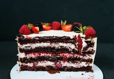 Cut creamy cake on black background, with strawberry raspberries. Dietary white from cream, with chocolate layers of. Cut creamy cake on a black background, with Stock Photo