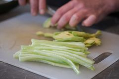 Cut cucumber and avocado. On the kitchen table with a sharp knife close up. Women`s hands Stock Photos