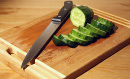 A cut cucumber and a knife Stock Image