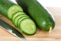 Cut cucumbers and knife. Two cucumbers cut into slices and a silver knife royalty free stock photography