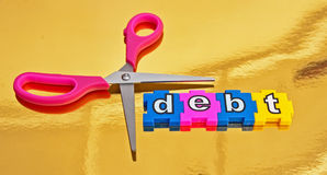 Cut debt. Scissors with pink handles with blades enclosing text ' debt ' in colorful  jigsaw style letters isolated on gold background Royalty Free Stock Images