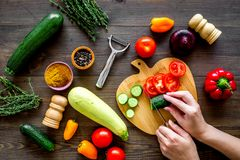 Cut different fresh vegetables on cutting board for cooking vegetable stew. Dark wooden background top view stock photo