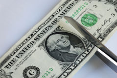 Cut the dollar bill with a scissors. Cut the daily expenses in various ways Stock Photography