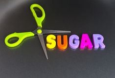 Cut down on sugar. Text ' sugar '  in colorful upper case letters ' surrounded '  by the blades of a pair of green scissors, and a concept of cutting down on Royalty Free Stock Photo